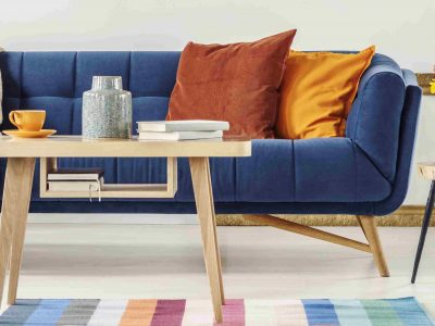 Closeup of a wooden table and a blue settee with orange pillows